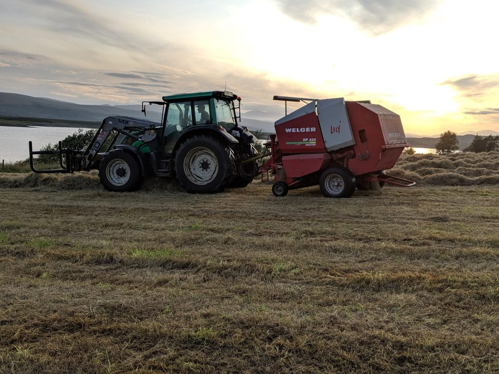 A tractor farming a field cultivating